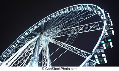 Brightly lit ferris wheel ride, which spinning at night or ...