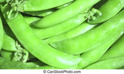 Brightly lit green peas turn left slow motion - Brightly...