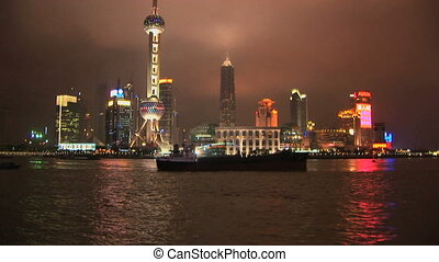 Brightly lit ship passing Shanghai, Pudong, time lapse