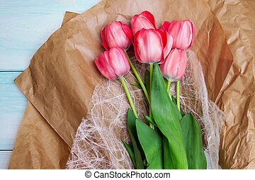 Brightly pink tulips lie on craft paper on a blue wooden background