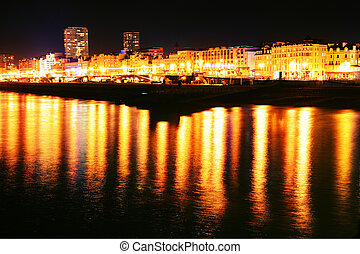 brighton seaside town in england. shoreline at night with sea and lit hotels