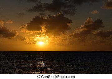 Brillian Orange Sun Setting Behind the Clouds