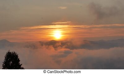 Brilliant summit dawn above flowing cloud waves, red sun...