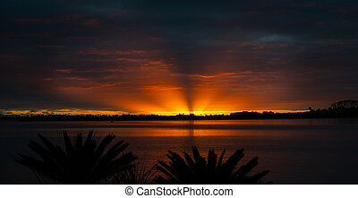 Brilliant sunrise through cloudy sky with rays of orange ...