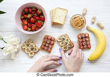 brinde, fazer dieta, ingredientes, leva, menina, sementes, amendoim, sobre, topo, saudável, jovem, vegan, above., fundo branco, manteiga, frutas, madeira, vista., concept., pequeno almoço
