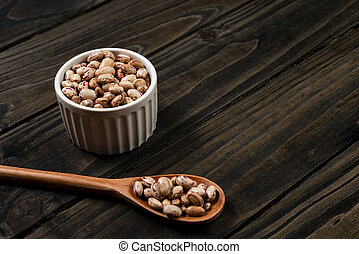 Brindle beans in pot. Wooden black background