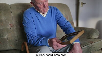 Senior man is sitting alone in the living room of his home, looking at an old photo.