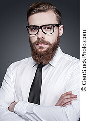 Bringing some creativity to business. Handsome young bearded man in shirt and tie keeping arms crossed and looking at camera while standing against grey background
