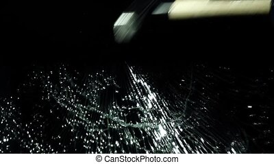 Brings a hammer to the glass and hits it, it crumbles into small pieces. Black background. Slow motion