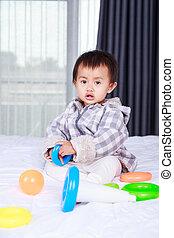 brinquedo bebê, tocando, cama