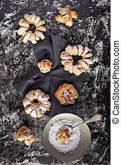 Brioches with icing sugar on dark background flat lay