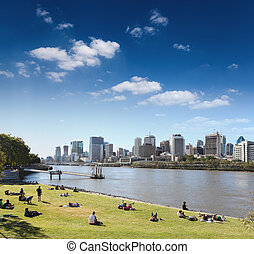 brisbane skyline from the park and people in lawn , ...