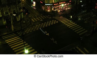 Brisk crossroads in the center of Paris, night life in city. France. Time lapse. Blurred advertising, license plates, faces, titles