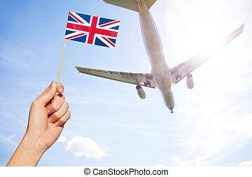 British flag against airplane flying through sky