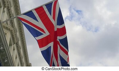 British flag close-up on a flagpole against a sky. - British...
