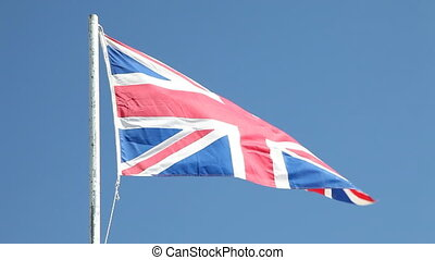 British flag waving in wind against clear blue sky