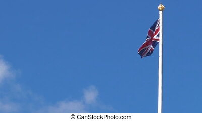 British flag with copy space in the wind and the blue sky. On a nice sunny day.