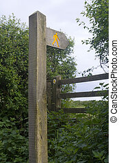 Yellow walker on wooden footpath signpost. Style and waymarker arrow in the background.
