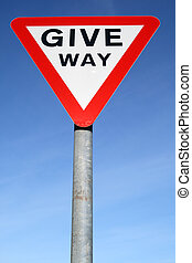 British give way road sign and a blue sky.