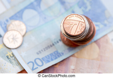 British one penny coin and 20 Euro note