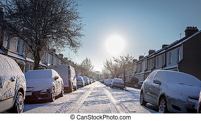 British Residential Street With Cars And Road Covered In Snow