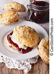 British scones with jam and whipped cream close-up. vertical