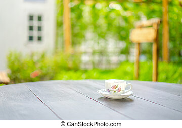 British tea cup style with drawing pink flower pattern on it, on the wood dark brown table in the morning with blur garden and window.