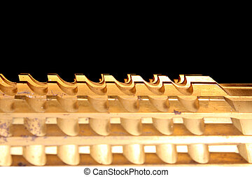 The pattern of grooves on a golden metallic industrial broach.