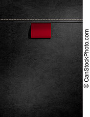 Broad Clothing Label In Black Leather - A red woven clothing...