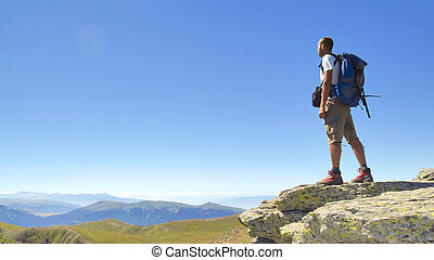Broad horizons - Male hiker standing with backpack on rock...