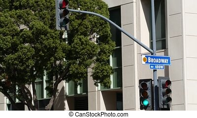 Broadway street name, odonym sign and traffic light on ...