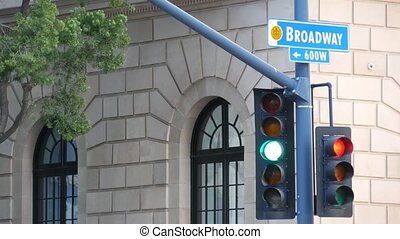Broadway street name, odonym sign and traffic light on pillar in USA. Road intersection in downtown of city. Crossroad in urban central business district. Nameplate banner with title of main avenue.
