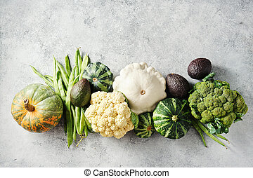 Broccoli, cauliflower, green beans, squash, and other fresh on a grey background.