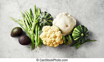 Broccoli, cauliflower, green beans, squash, and other fresh vegetables on a grey background.