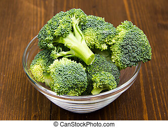 Broccoli in glass bowl on wooden table