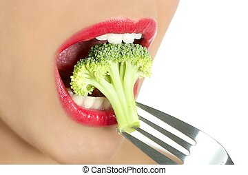 Broccoli on steel fork in woman mouth