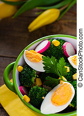 Broccoli salad with tulip flowers on wooden background.