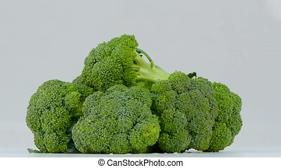 Broccoli spinning on a white background - a rotating pile of...