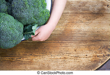 Broccoli - Large bowl of fresh broccoli being held by a...