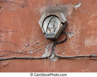 brocken streetlamp on an aged red wall