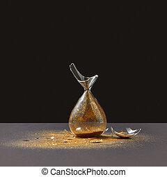 Brocken vintage sandglass with golden sand on a black ...