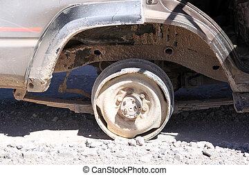 Brocken wheel of the dusty car in desert