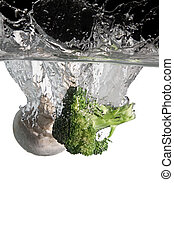 brocoli and mushroom thrown in water with black and white background