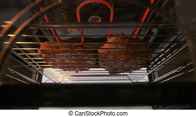 Broiling beef marbled steaks in the oven with broiler. Grill element glowing red. Juicy grilled ribeye steaks on grilling rack under high heat. Meat juices dripping onto a drip pan.