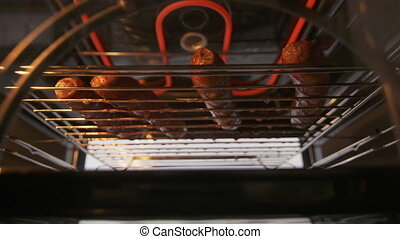 Broiling beef sausages in the oven with broiler. Rack with...