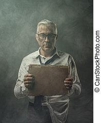 Broke jobless businessman holding a cardboard sign
