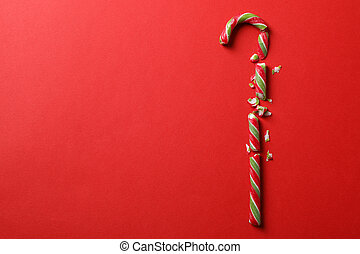Broken candy cane on red background, space for text