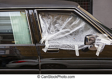 Broken car window covered with plastic