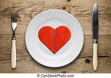 Broken cardboard heart on plate on wooden background
