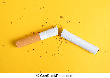 Broken cigarette in half on a yellow background. Top view.